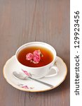 Cup of herbal tea with flowers on a wooden background. - stock photo