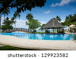 pool with artificial beach and tropical ocean - stock photo