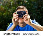 man with a vintage camera take... | Shutterstock . vector #1299507628