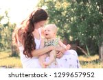 mom talking to the baby sitting ... | Shutterstock . vector #1299657952