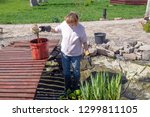 Woman Cleans The Garden Pond....