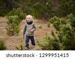 cute little boy walks in swiss... | Shutterstock . vector #1299951415
