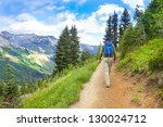 Male hiker walking up the trail in the mountains near Mt. Rainier with blue backback. - stock photo