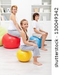 Happy family - woman and kids - exercising at home using gymnastic balls - stock photo