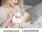 young mother feeding her little ... | Shutterstock . vector #1300509838