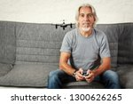 senior man playing with a drone | Shutterstock . vector #1300626265