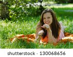 girl is lying on the green grass and smiling - stock photo