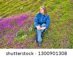 woman sitting in a field of... | Shutterstock . vector #1300901308