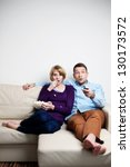 Scared young couple watching tv - stock photo