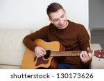 Handsome young man playing guitar, sitting on sofa - stock photo