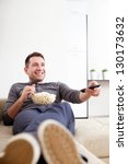 Single man on the couch watching tv, changing channels - stock photo