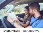 happy couple traveling by car... | Shutterstock . vector #1302009292