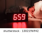 Small photo of Alarm clock on the bedside table with red numbers, sleeping man in bed in dark room. Concept chef sleeping after hard day at restaurant, sleep disturbance, oversleep work, night shift