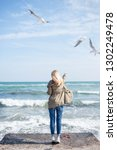a girl stands on the beach and... | Shutterstock . vector #1302249478