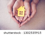 hands holding yellow house ... | Shutterstock . vector #1302535915