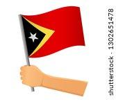 east timor flag in hand.... | Shutterstock .eps vector #1302651478