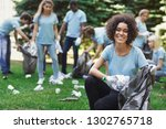 Small photo of Volunteering, charity and clean environment concept. Happy black woman and group of volunteers with garbage bags cleaning area in park, copy space