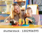 nursery baby and carer play at... | Shutterstock . vector #1302906595