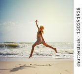 happy girl jumping on the beach ... | Shutterstock . vector #130291928