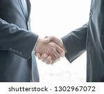 two businessmen shaking hands... | Shutterstock . vector #1302967072