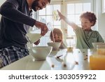 father making breakfast for his ... | Shutterstock . vector #1303059922