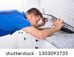 mature repairman installing... | Shutterstock . vector #1303093735