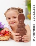Happy easter girl with chocolate bunny and dyed eggs - closeup - stock photo