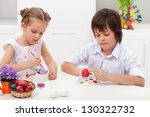 Children painting easter eggs sitting at the table - stock photo