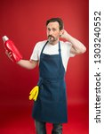 man in apron with gloves hold... | Shutterstock . vector #1303240552