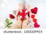 Valentine Gift. Young Couple Hands holding gift box with red bow gift over wooden background. St. Valentine