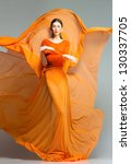 beautiful woman in long orange... | Shutterstock . vector #130337705