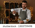 barman pouring wine from bottle ... | Shutterstock . vector #1303759498