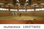 young girl riding horse indoors....   Shutterstock . vector #1303776052