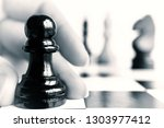 a black pawn stands on a...   Shutterstock . vector #1303977412