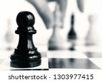 a black pawn stands on a...   Shutterstock . vector #1303977415