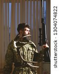 Small photo of Gamekeeper concept. Man with beard wears camouflage clothing, curtains background. Hunter, brutal hipster with gun and horns of deer. Macho on strict face at gamekeepers house ready for hunting.