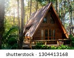 Small photo of Little wooden cottage house in forest. Log cabin hut with garret and giant pinewood trees in the morning sunlight.