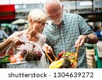 smiling senior couple holding... | Shutterstock . vector #1304639272
