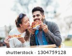 couple eating pizza outdoors... | Shutterstock . vector #1304759128
