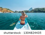 woman paddling a kayak by the... | Shutterstock . vector #1304824435