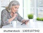 portrait of senior woman using... | Shutterstock . vector #1305107542