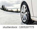 the wheel of a car on a snowy... | Shutterstock . vector #1305207775