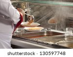 Stock photo chef standing behind full lunch service station 130597748