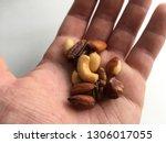 handful of mixed nuts hand... | Shutterstock . vector #1306017055