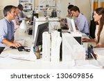 Team Working At Desks In Busy...