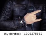 Man hand holding microphone. Leather  bracelet and accessory .Hard rock, heavy metal,gothic and punk style.Brutal jacket - stock photo