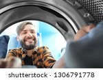 man doing laundry in laundromat ... | Shutterstock . vector #1306791778