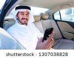 happy positive arab man holding ...   Shutterstock . vector #1307038828