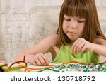 Young girl making bead bracelets - stock photo