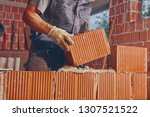Real construction worker bricklaying the wall indoors. - stock photo